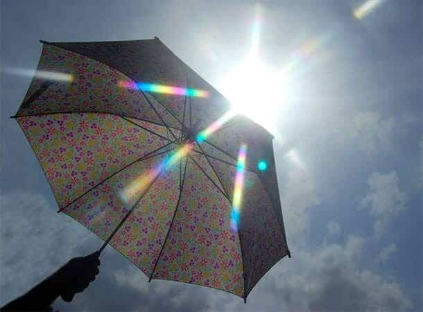 Bright sunlight being shielded by an umbrella