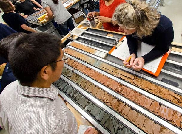 Scientists examine the working and archive halves of a freshly split core. Credit: Tim Fulton, IODP, JRSO