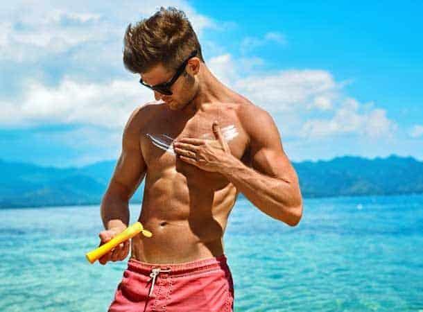 Buff man applying sun lotion